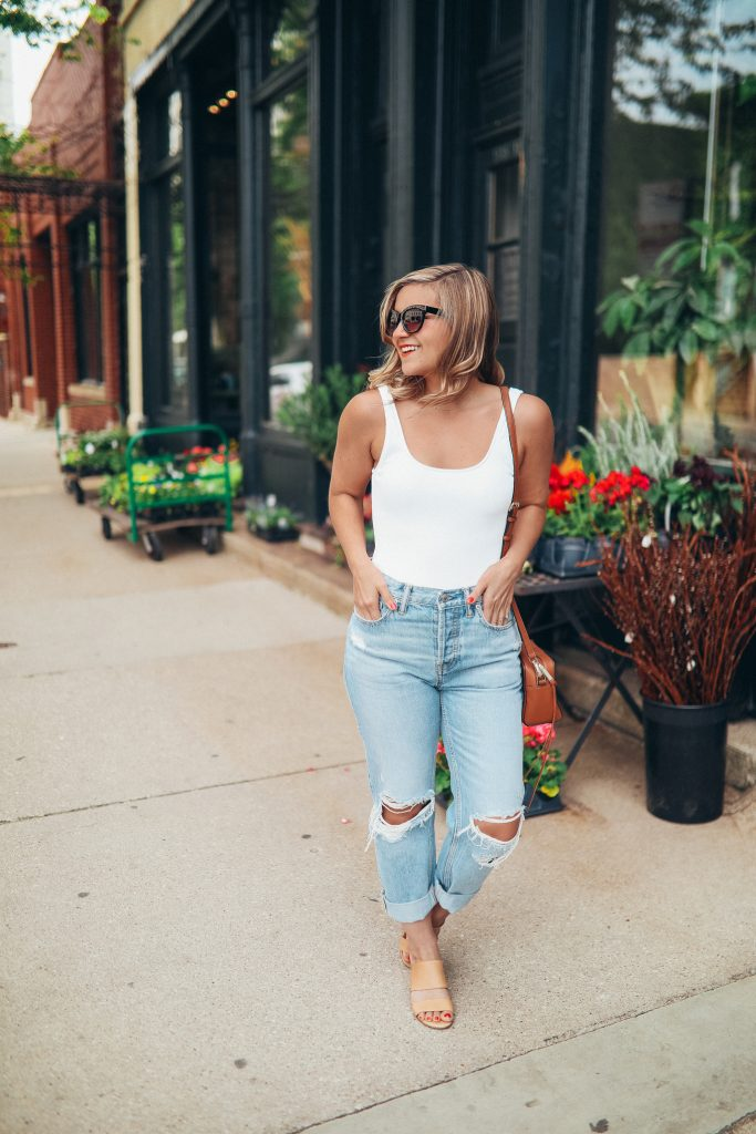 Distressed jeans and white bodysuit featured
