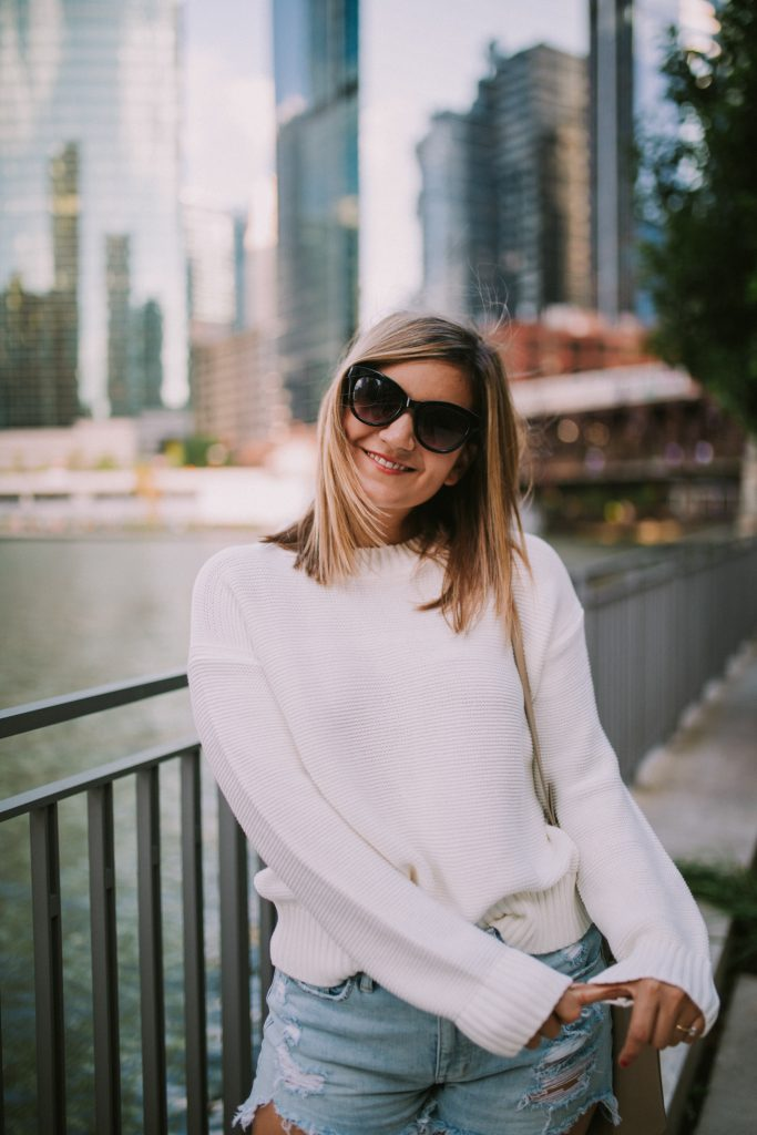 a woman with sunglasses and a view of the water behind her