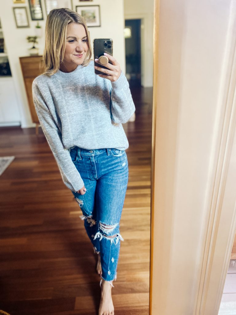 woman wearing grey sweater and jeans