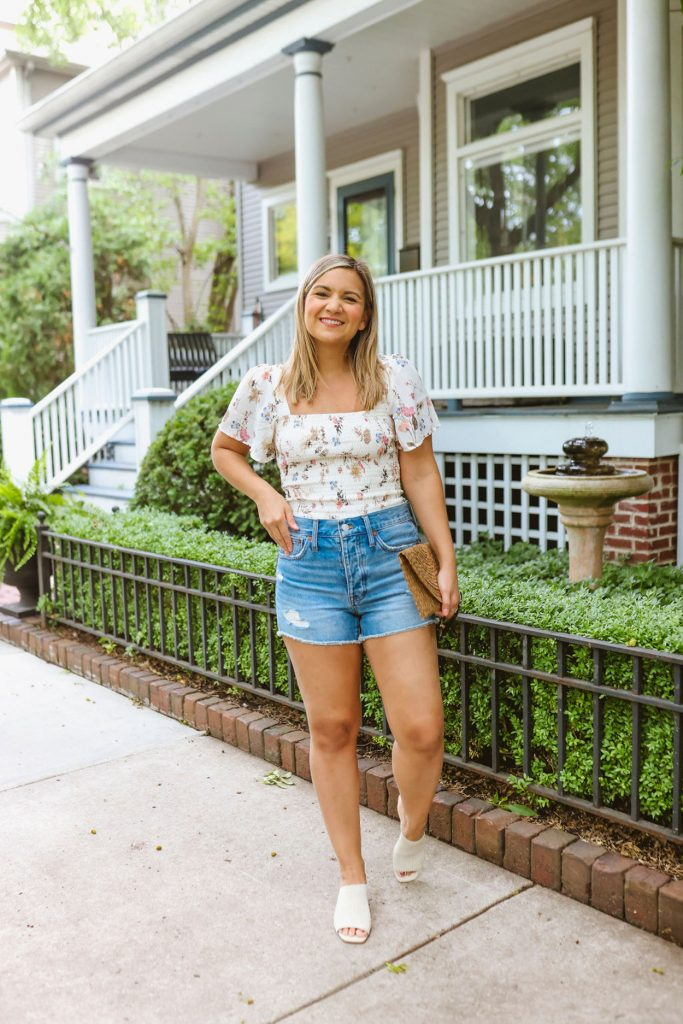 woman wearing floral top and denim shorts