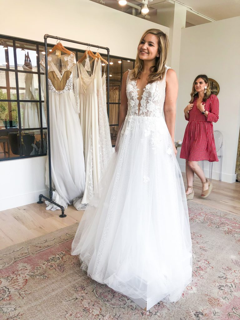 woman trying on a wedding dress with an assistant