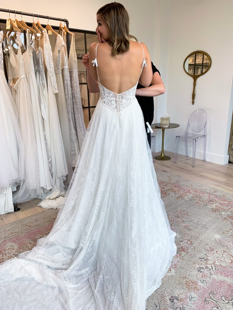 back details of woman trying on and sharing Wedding Dress Shopping Tips