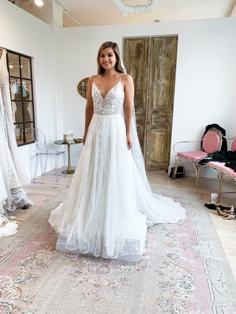 woman smiling while trying on her wedding dress