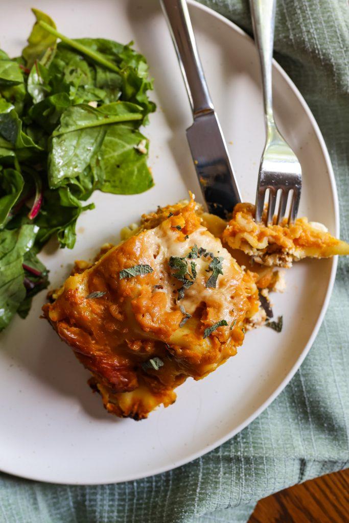 top view of a slice of crockpot pumpkin lasagna and vegetables