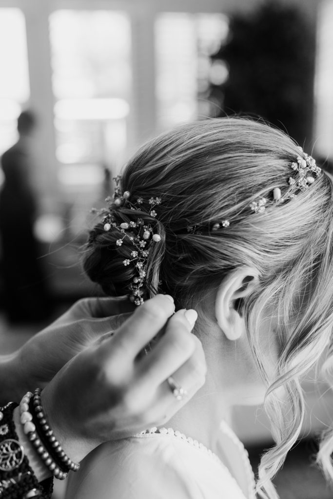 woman adding wedding hair piece